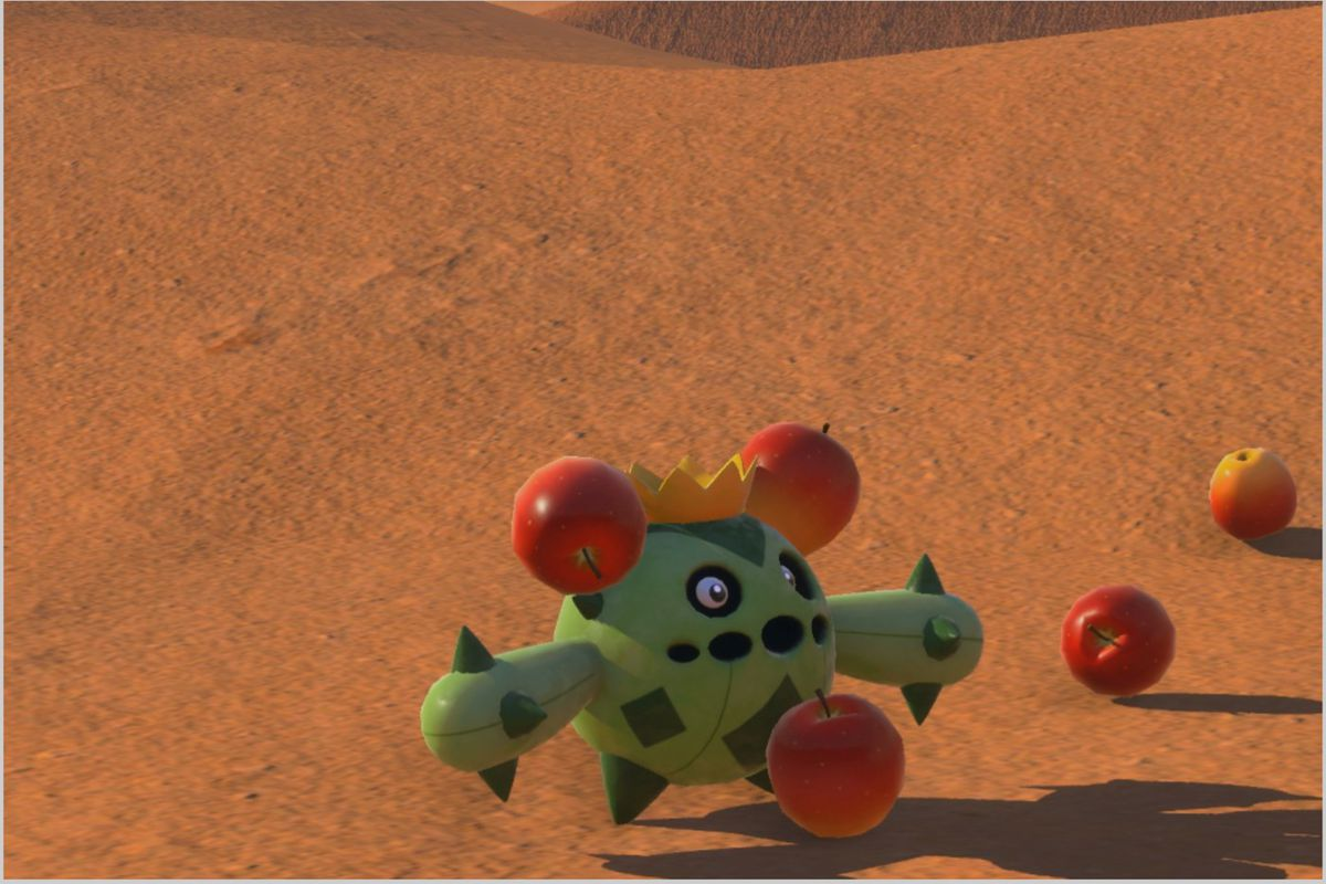 A Cacnea with several fruit stuck to its head stands in a desert
