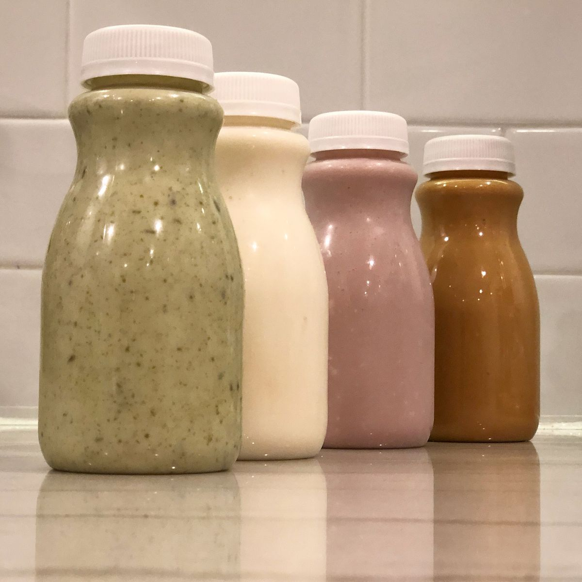 four bottles of drinkable yogurt and kefir, in pistachio, strawberry, vanilla, and salted caramel flavors