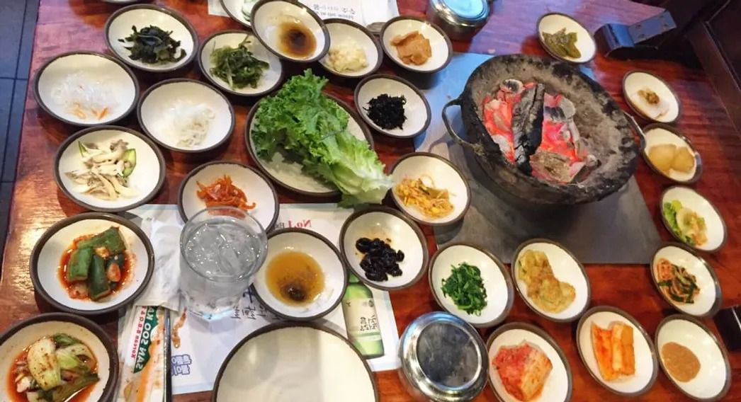 A charcoal grill and various banchan on a table.