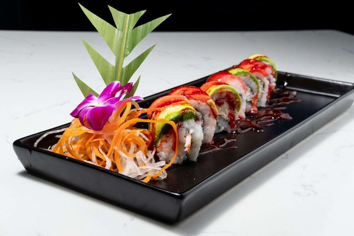 A rice-wrapped sushi roll on a black tray garnished with julienned veggies and a flower