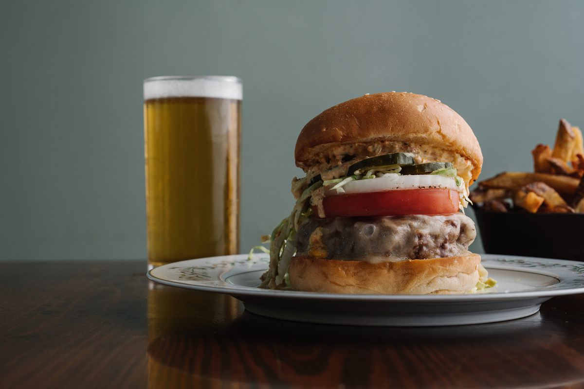 A double cheeseburger with lettuce, tomatoes, pickles, and onions with a glass of pilsner beer and a side of hand-cut fries