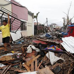 Edwin Dapon carries a bed frame through the rubble in Tacloban, Friday, Nov. 22, 2013.