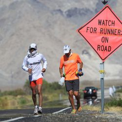 Ray Sanchez (L) of Sacramento, California runs along highway 136 north of Lake Owens as he approaches the town of Lone Pine during the AdventurCORPS Badwater 135