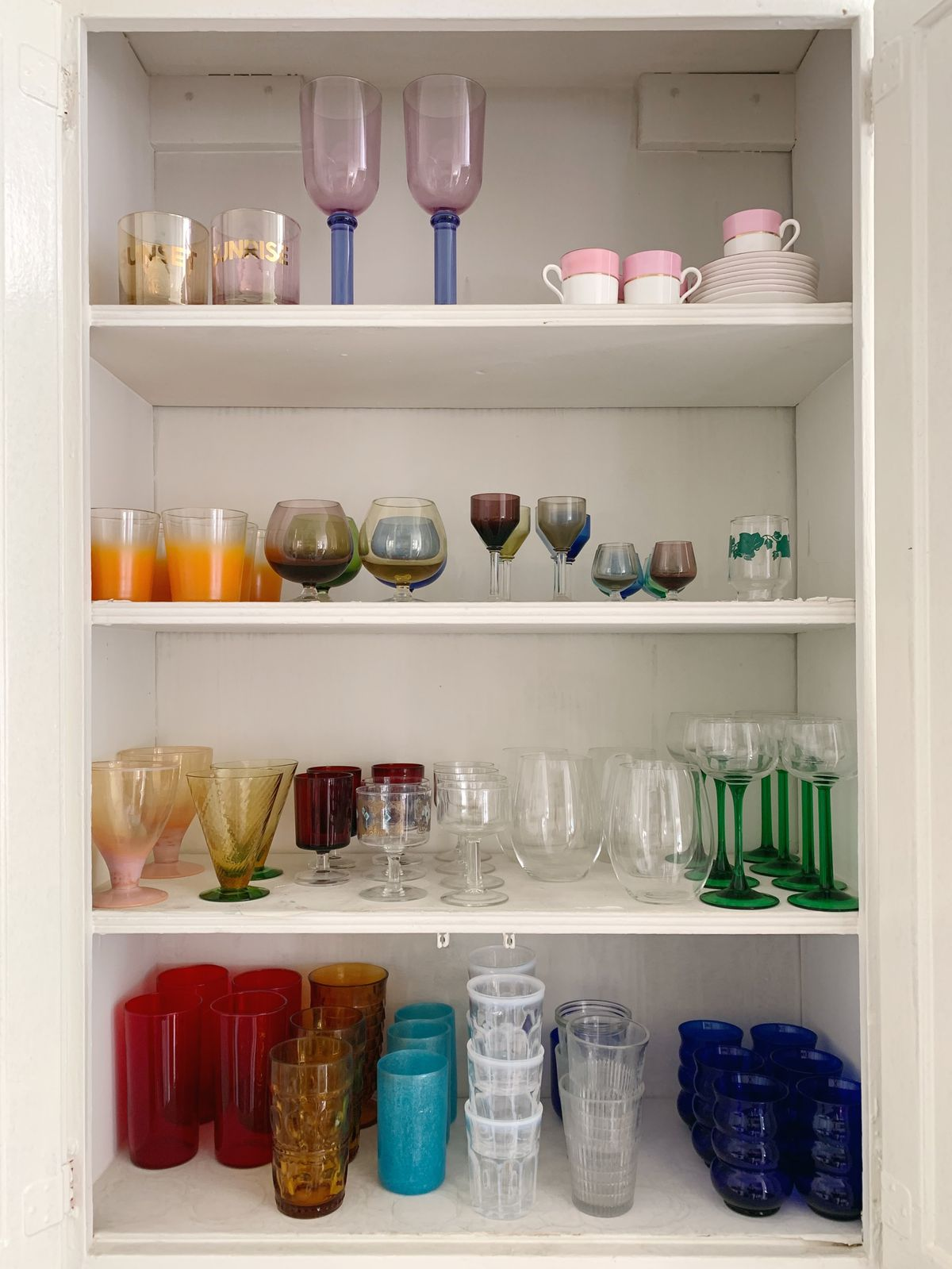 A four-tiered white cabinet holds a collection of colored glass in shades of purple, orange, yellow, green, red, blue, and white.