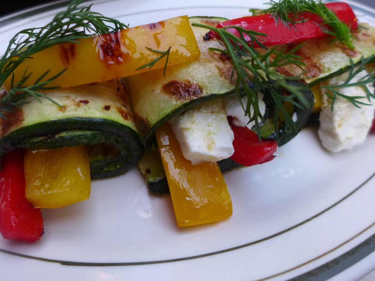 Rolls of summer squash stuffed with yellow bell pepper and white cubes of cheese, topped with fresh dill.