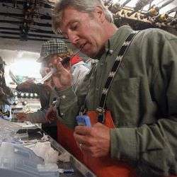 In this Sept. 13, 2012, photo, Massachusetts shark expert Greg Skomal pulls the cap off a blood sample taken from an Atlantic great white shark before performing blood gas analysis moments after the nearly 15-foot, 2,292-pound shark was released from the research vessel Ocearch off the coast of Chatham, Mass. The Ocearch team baits the fish and leads them onto a lift, tagging and taking blood, tissue and semen samples up close from the world's most feared predator. The real-time satellite tag tracks the shark each time its dorsal fin breaks the surface, plotting its location on a map.