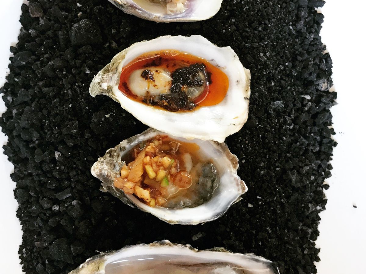 From above, four clams and oysters of various sizes and shapes, topped with sauces and ground toppings, sit on a long plate atop small black rocks