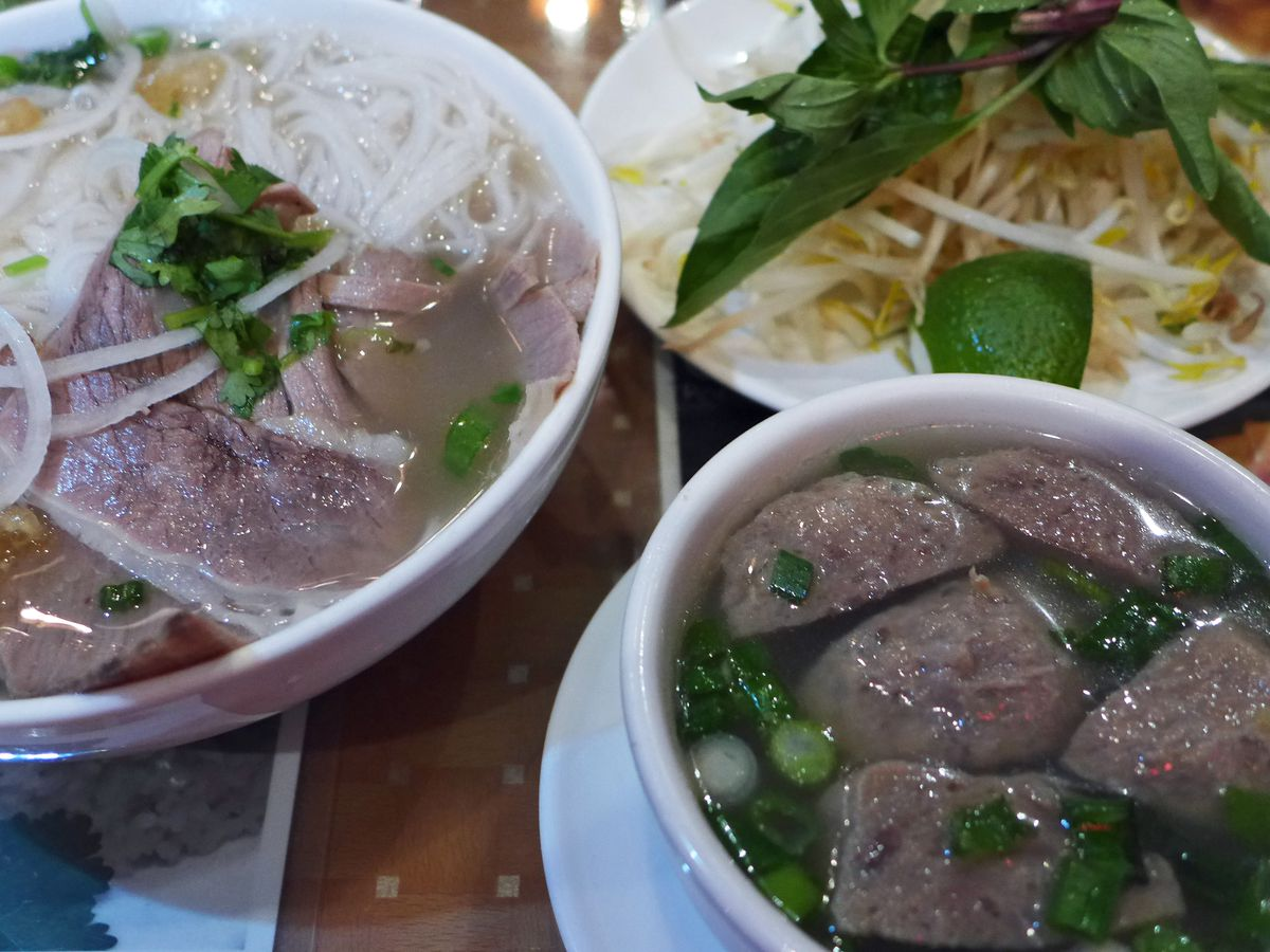 A bowl of pho with a smaller bowl of beef balls on the side.