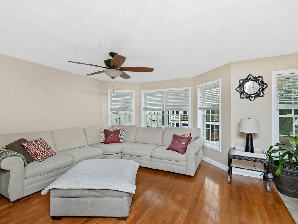 A spacious living room with a sectional couch and a bay window.
