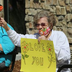 Priscilla Cahoon smiles and waves back at her grandchildren Katelyn Pettit, Jann Campbell and Carolyn Spencer, as residents at The Ridge Cottonwood senior living center in Holladay watch as family members parade with signs, balloons and waves for Mother's Day on Saturday, May 9, 2020.