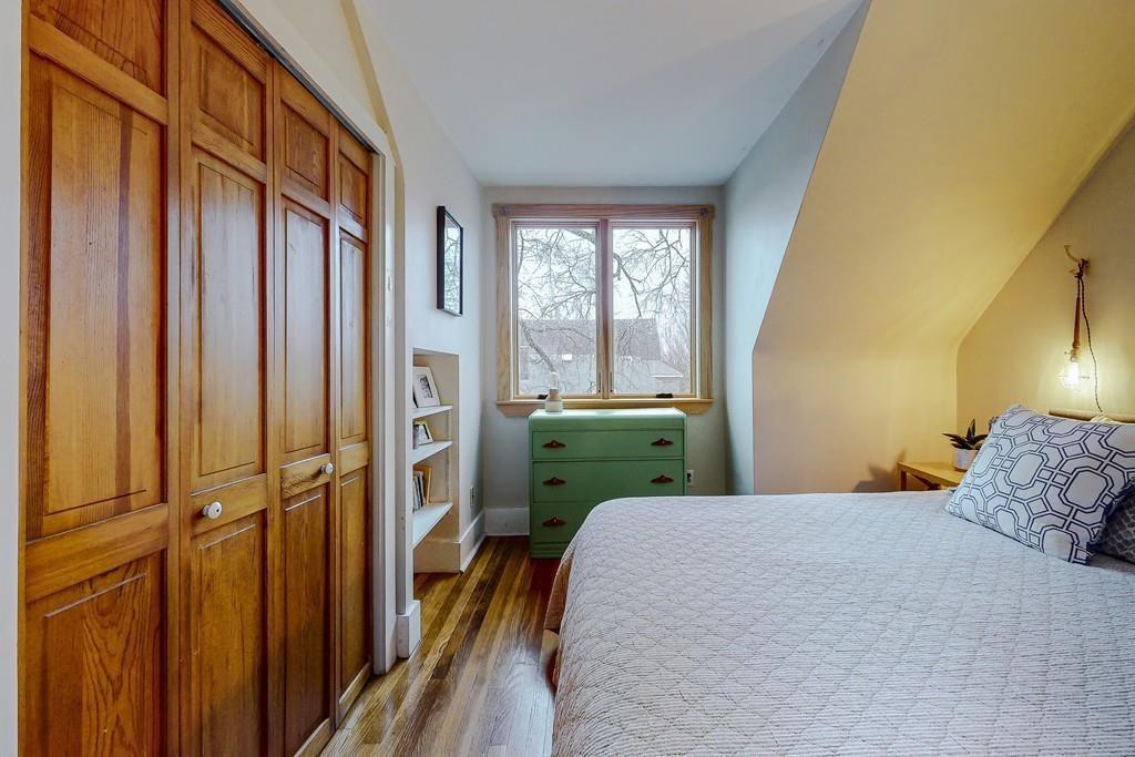 A bedroom with a bed facing a closed closet door.
