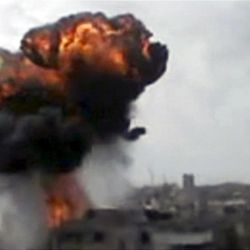 In this image made from amateur video released by the Shaam News Network and accessed Sunday, April 15, 2012, smoke billows an impact following purported shelling in Homs, Syria. Syrian troops are reported to have shelled residential neighborhoods dominated by rebels in the central city of Homs Sunday, activists said, killing at least three people hours before the first batch of United Nations observers were to arrive in Damascus to shore up a shaky truce.