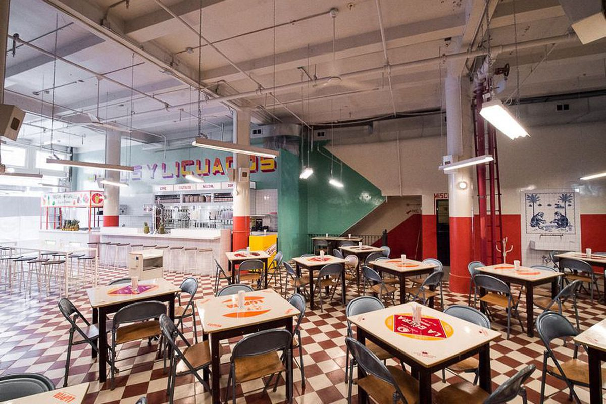 Inside one of the locations of the taco chain Tacombi where black and white tables sit on checkered floors
