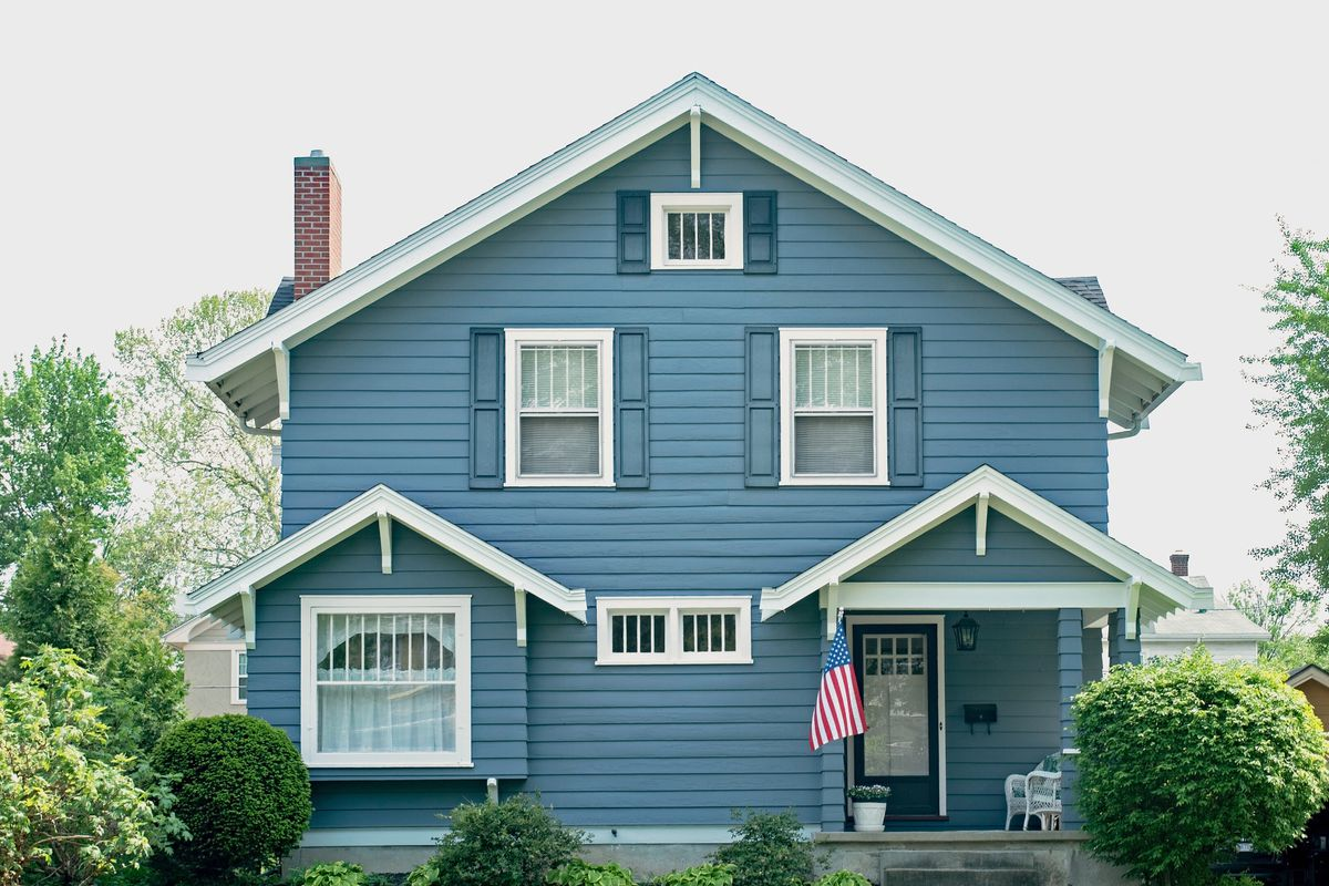 Exterior of a blue house with an American flag flown off the front porch. Greenery and shrubs surround the home.