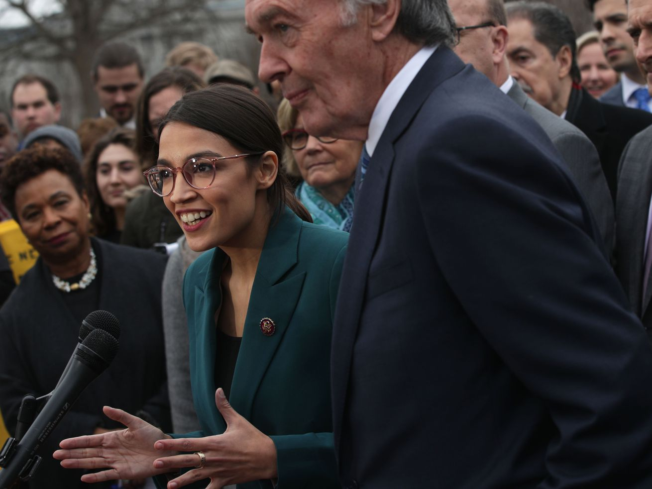 Rep. Alexandria Ocasio-Cortez (D-NY) speaks as Sen. Ed Markey (D-MA) and other congressional Democrats listen during a news conference in front of the US Capitol on February 7, 2019, in Washington, DC.