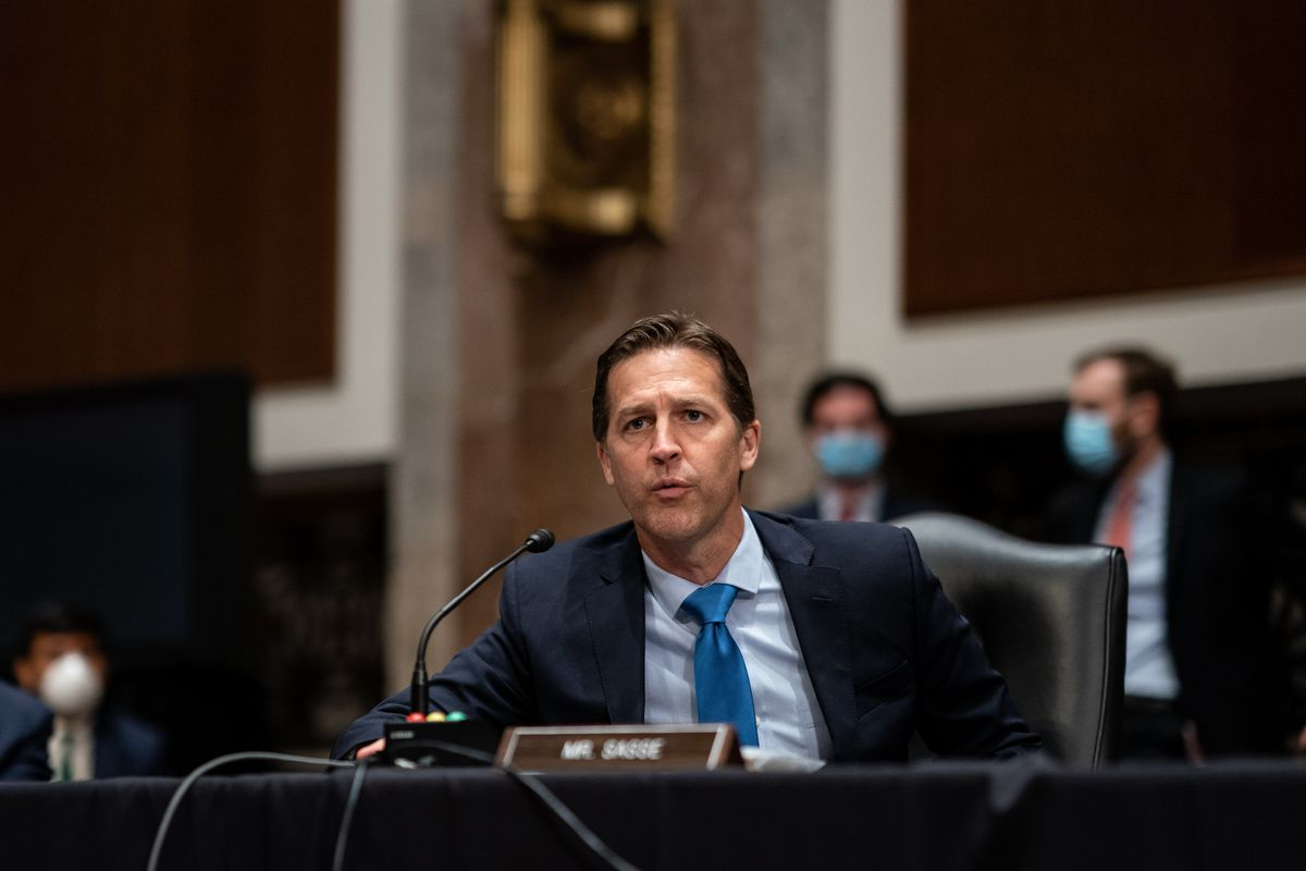 Sasse, clean shaven, and in a dark suit, blue shirt, and blue tie, speaks emphatically into a microphone while seated behind a black-draped table.