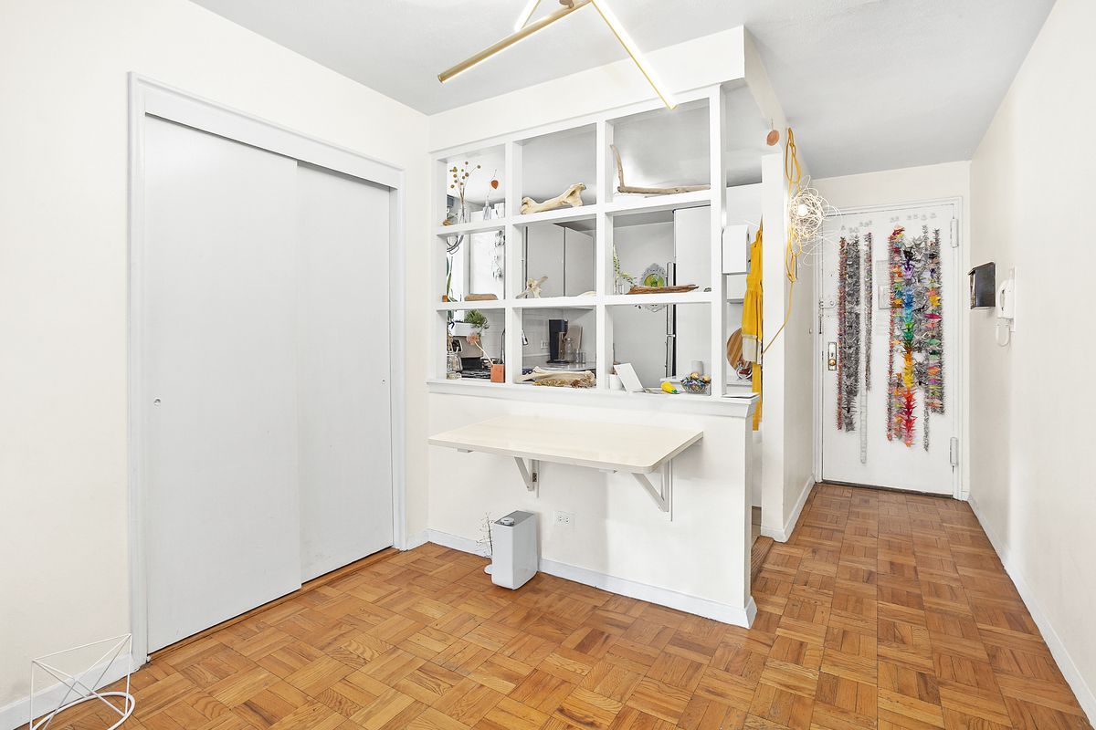 A living area with a closet and a kitchen in the back.