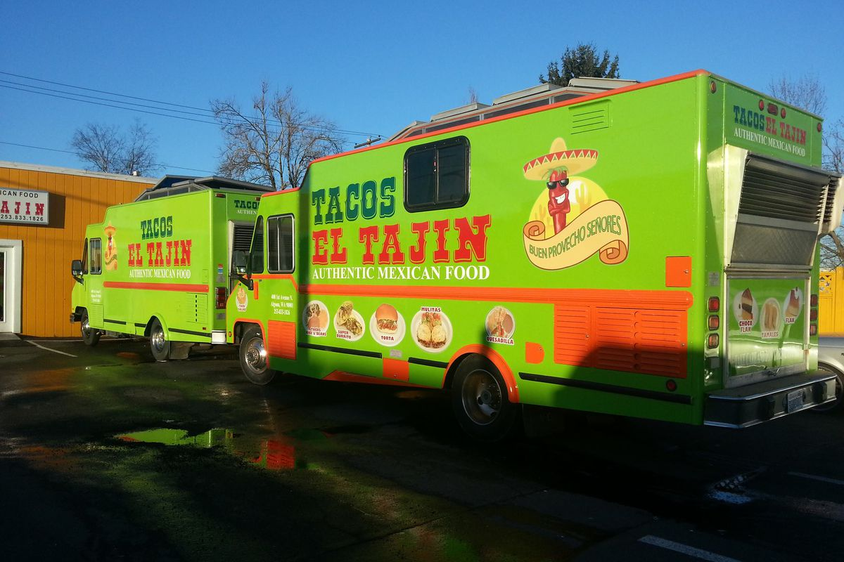 A view of the green Tacos El Tajin food truck, painted green with a cartoon pepper on the side