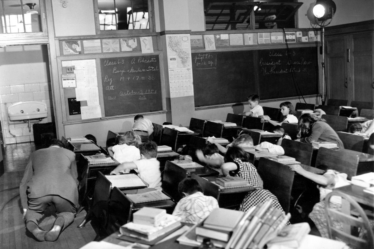 Children and a teacher in a classroom in the 1950s practice an air raid drill.