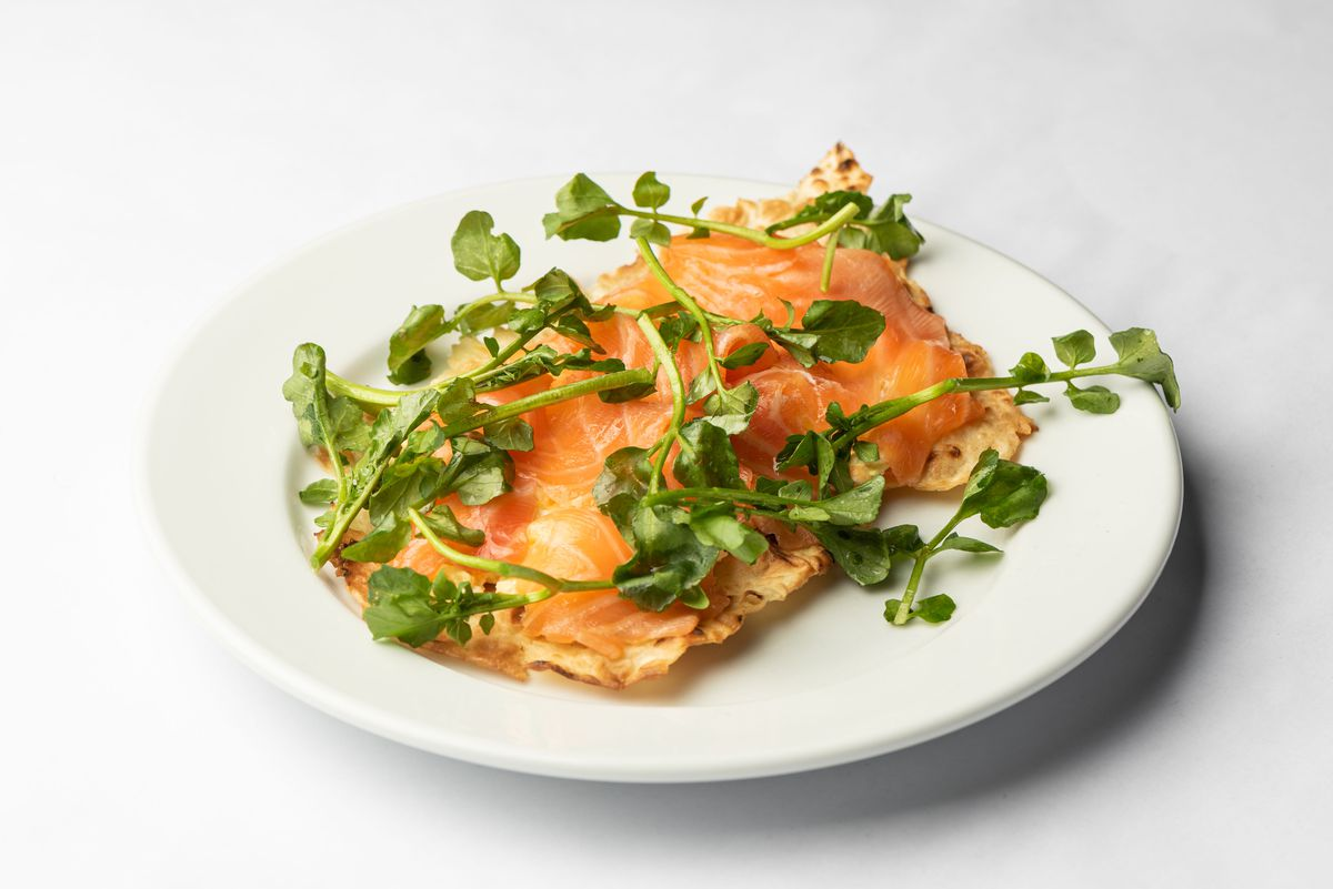Salmon with greens on a thin piece of bread atop a white plate.