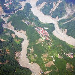The aerial handout photo taken and provided by Taiwan's Military News Agency on Tuesday shows houses engulfed by massive landslides on a mountain of Alishan, a scenic township in the southern Chiayi county. Soldiers searched typhoon-devastated areas for survivors and bodies as more than 1,600 people waited to be airlifted to safety 10 days after Typhoon Morakot struck Taiwan.