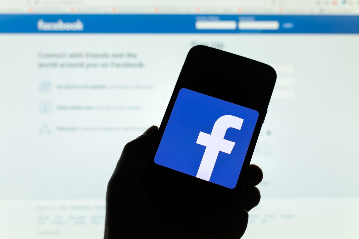 Photo illustration a Facebook logo displayed on a phone screen.