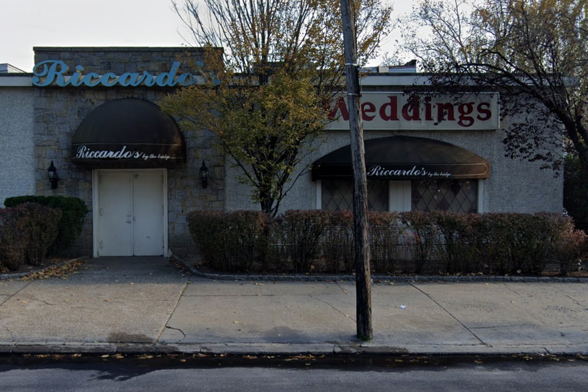 """A wedding venue and event space sits on a street with a cursive blue sign that reads """"Riccardo's"""""""