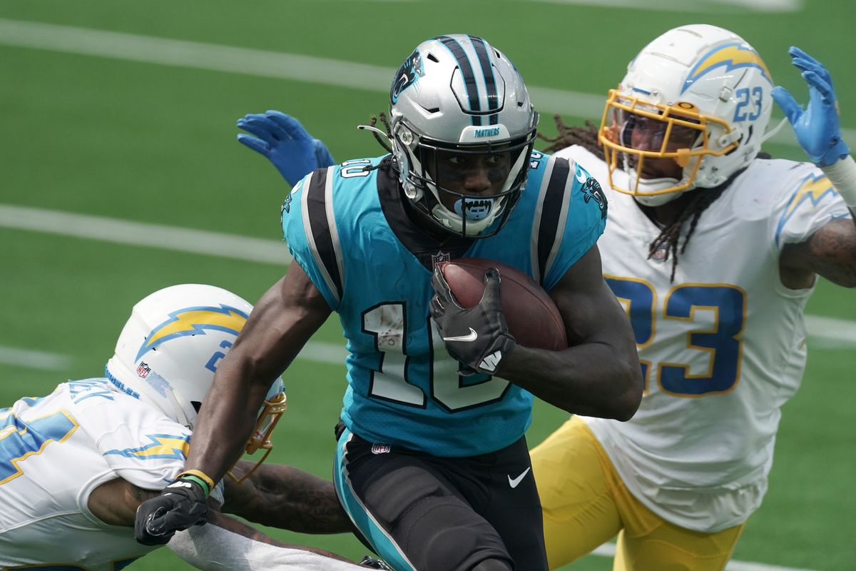 Carolina Panthers wide receiver Curtis Samuel (10) is pursued by Los Angeles Chargers strong safety Rayshawn Jenkins (23) and safety Nasir Adderley (24) in the first half at SoFi Stadium.