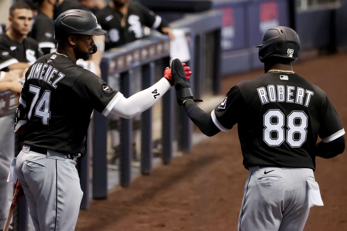 Eloy Jimenez #74 and Luis Robert #88 of the Chicago White Sox celebrate after Robert scored a run in the first inning against the Milwaukee Brewers at Miller Park on August 03, 2020 in Milwaukee, Wisconsin.