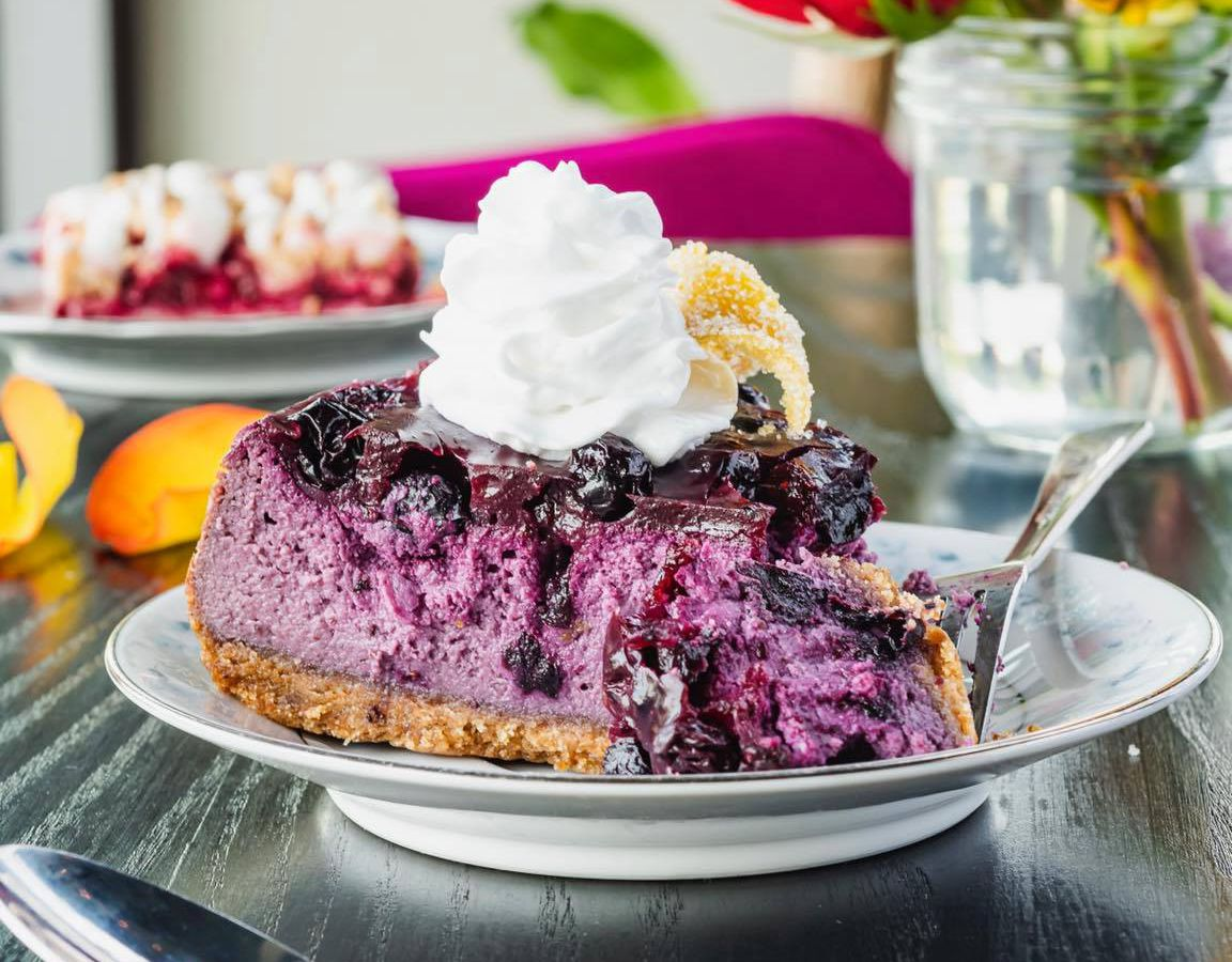 A spoon dipping into a slice of bright blue cheesecake topped with whipped cream on a table beside other desserts