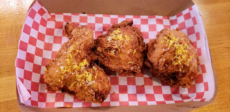 Three pieces of craggly fried chicken resting on a red checkered tissue-lined box.