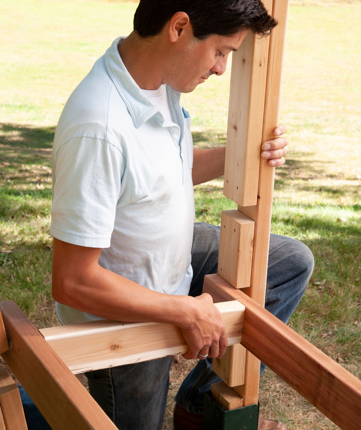 Man Attaches Base And Lower Crosspieces Of Arbor Bench