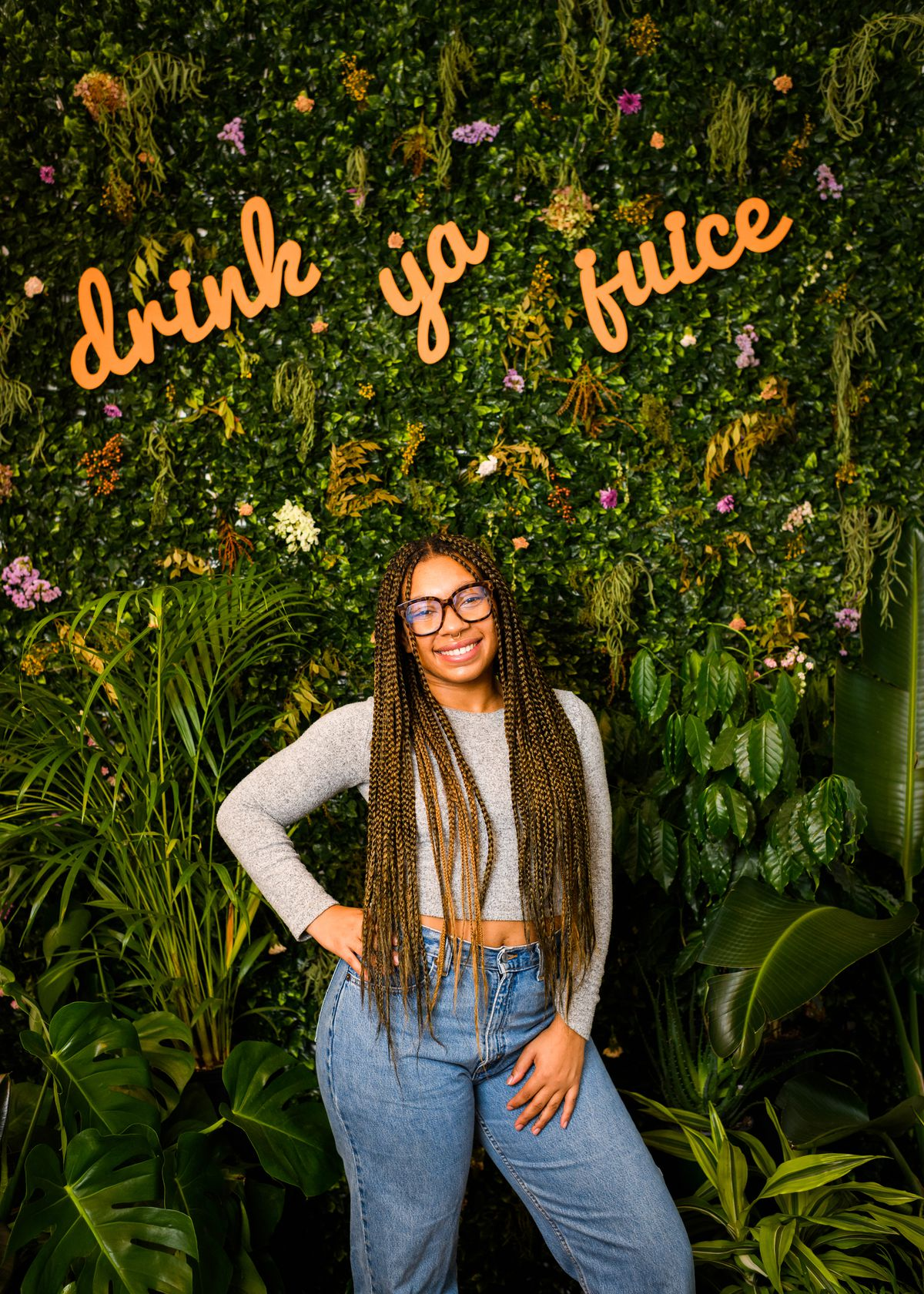 """A woman in a grey shirt and blue jeans stands in front of a wall of plants. The words """"drink ya juice"""" are mounted among the plants."""