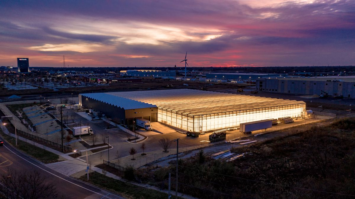 At sunset, an aerial view of the greenhouse with lights inside and delivery trucks out front.