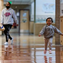 Akesa Palie, 2, followed by her mother Vika Palei carrying new donated shoes for her, reacts while running in the hallway on Thursday, Sept. 16, 2021, at Mountain View Elementary School in Salt Lake City. The Larry H. & Gail Miller Family Foundation donated 1,000 pairs of Asics running shoes to underserved girls participating in the Girls on the Run Utah character development program.