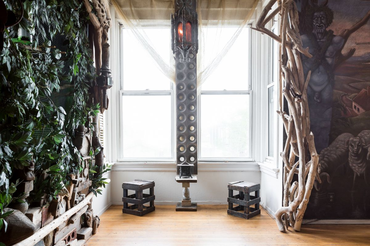 On one side of the room is a wall of plants. On the other side of the room is a wooden structure with a mural. The windows have chairs in front of them. There is a hanging ornamental light fixture.