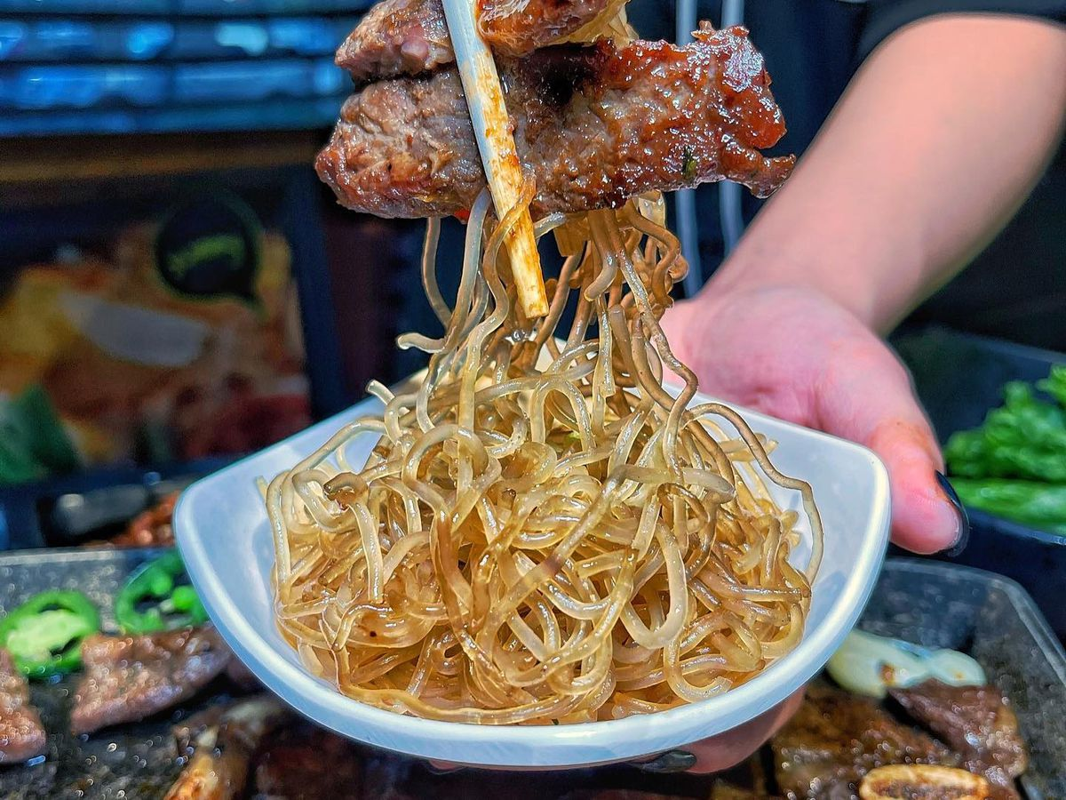 a hand with chopsticks holding two pieces of cooked meat and a big glob of glass noodles
