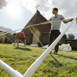 LDS missionaries Elders Jacob Holden and Carter Sanders help Catholics set up for the Carmelite Fair at the monastery in Holladay Tuesday, Sept. 16, 2014.