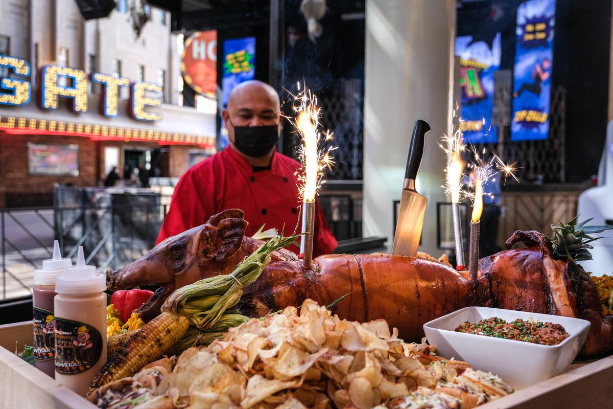 A man in a red jacket and a mask stands in front of a barbecued pig with sandwiches around it.