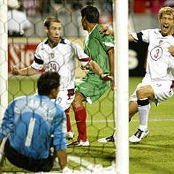 USA's Steve Ralston (19) backs out of the net after scoring against Mexico's goalie Oswaldo Sanchez.
