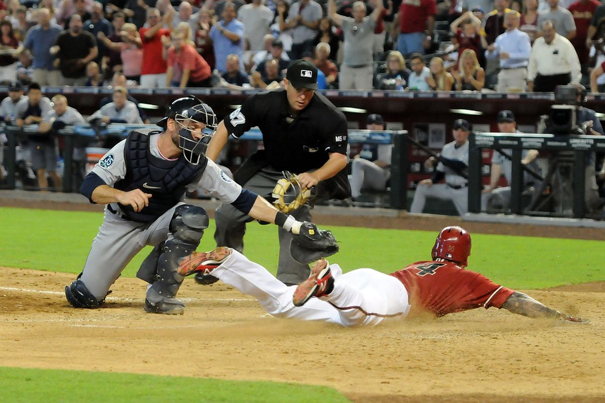 PHOENIX, AZ - JUNE 20:  Ryan Roberts #14 of the Arizona Diamondbacks slides safely into home plate ahead of a tag by John Jaso #27 of the Seattle Mariners at Chase Field on June 20, 2012 in Phoenix, Arizona.  (Photo by Norm Hall/Getty Images)