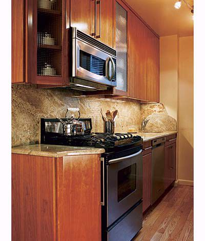 Bright and well lit kitchen stove top and cabinets.