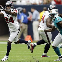 Houston Texans cornerback Johnathan Joseph intercepts a pass as Miami Dolphins wide receiver Legedu Naanee watchesn in the second quarter of an NFL football game, Sunday, Sept. 9, 2012, in Houston.