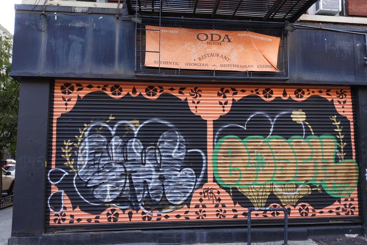 """The steel grates of a restaurant are decorated in orange graffiti, while a banner hangs above with the words """"Oda"""""""