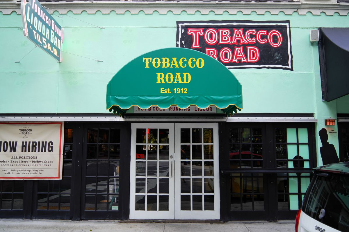 Green Entry way with sign that says Tobacco Road with white doors and black lined windows