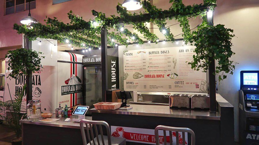 Ivy-covered food stall selling burrata cheese sandwiches at LA's Grand Central Market.