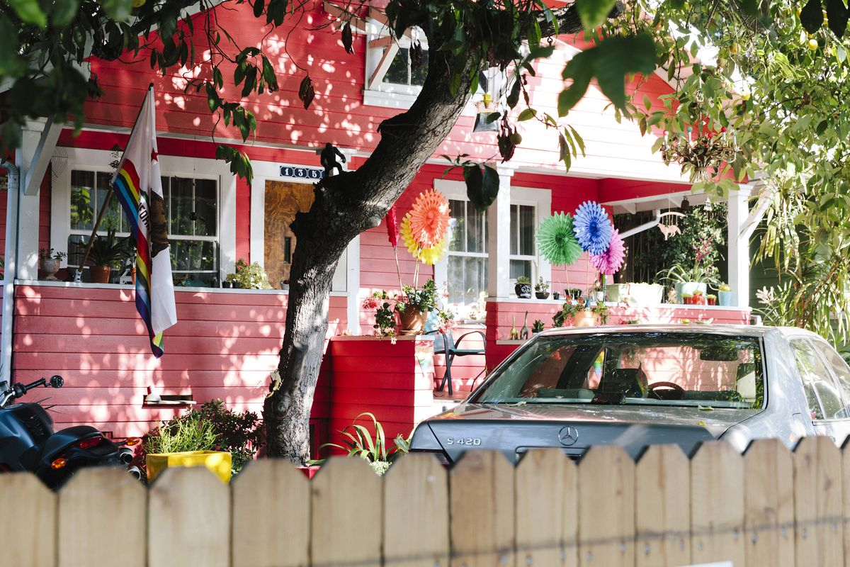 Red bungalow style house with a porch and lots of flags, plants and colorful decorations outside. A big tree in the front yard frames the home. A wooden fence and car in front of the home as well.