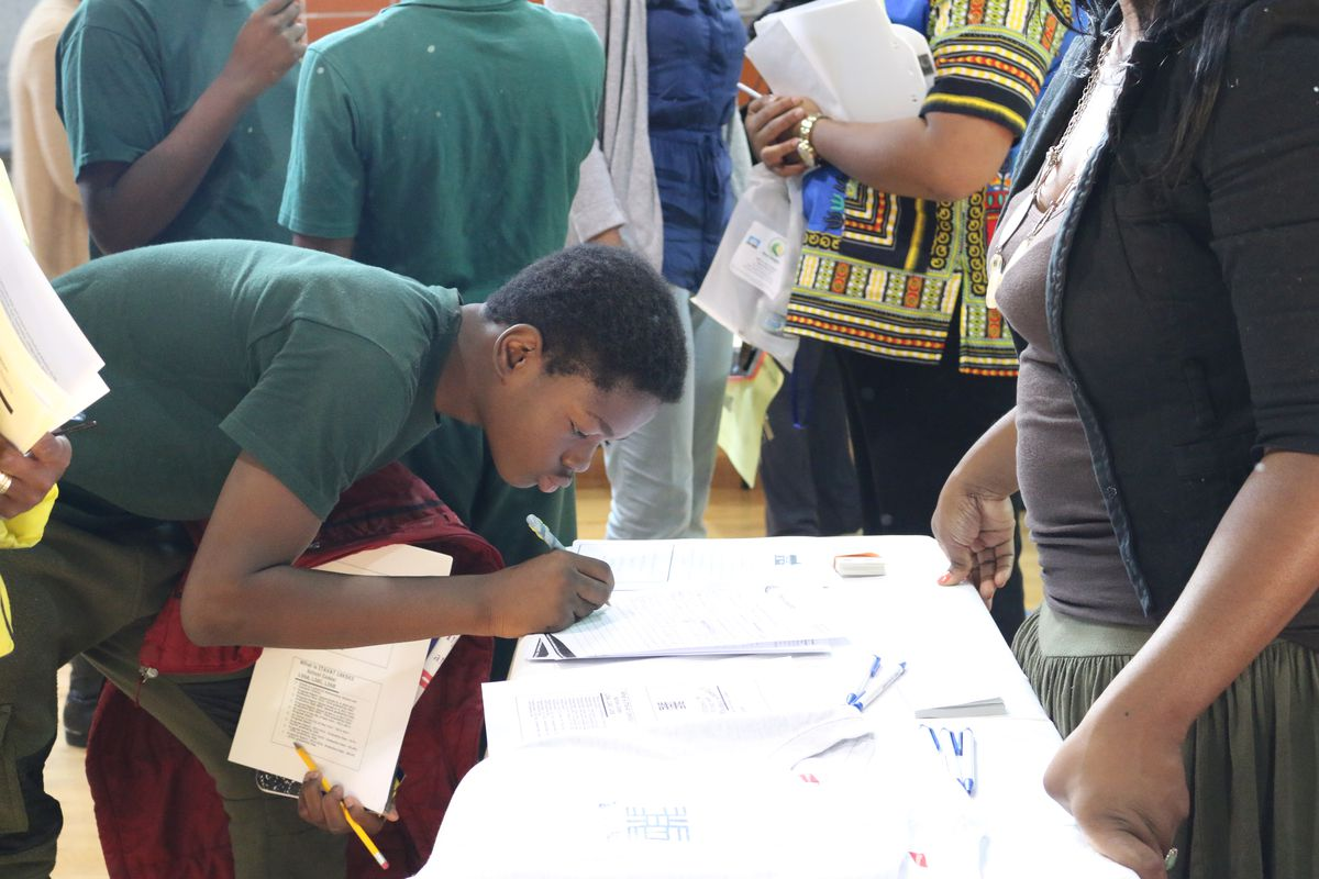 A student signs his name at a high school fair at New Heights Middle School