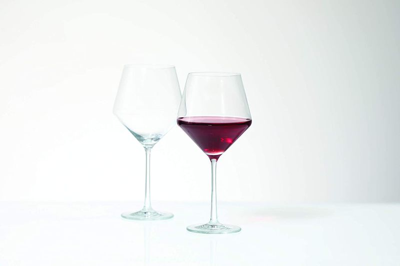 Two wine glasses, one empty, one filled with red wine
