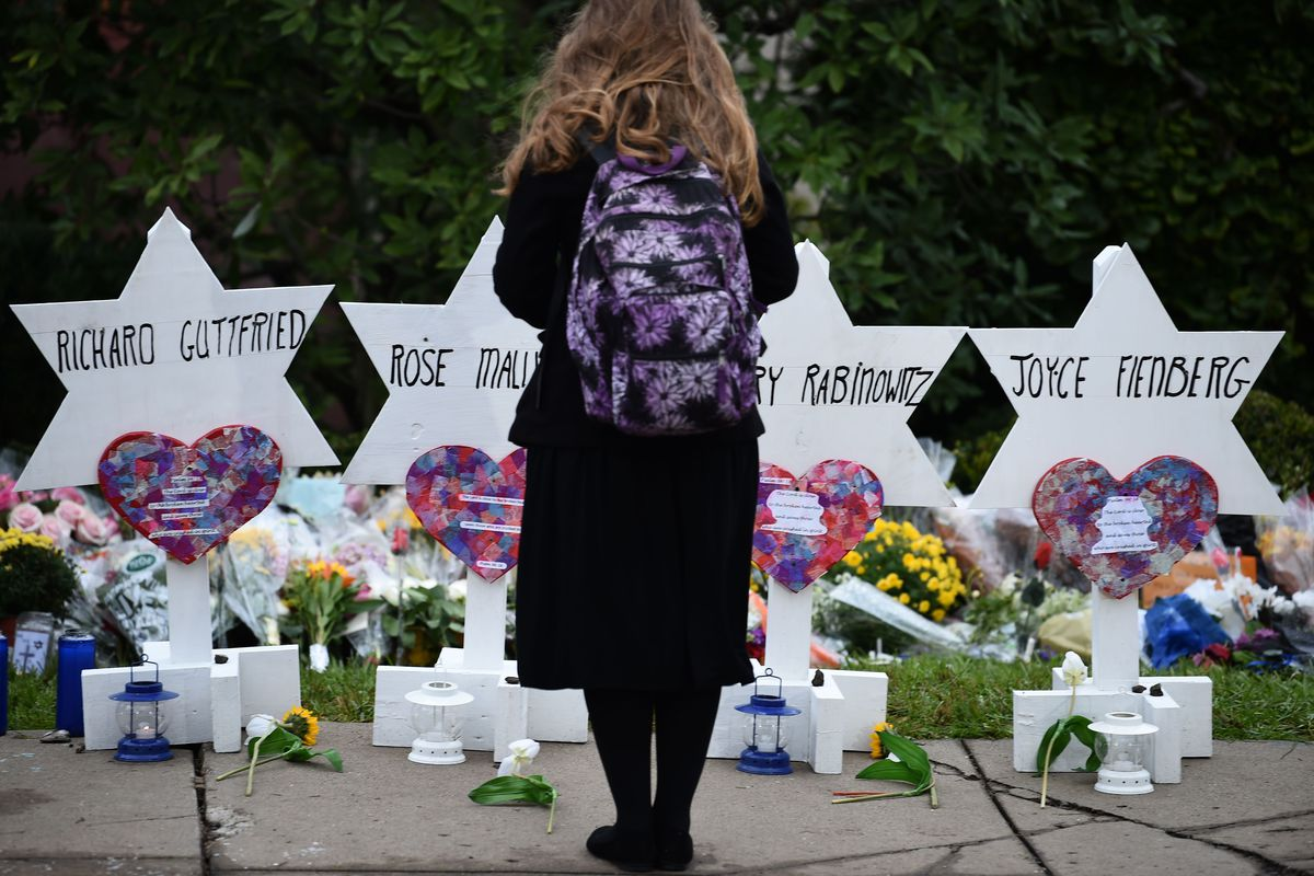 A woman stands at a memorial outside the Tree of Life synagogue after a shooting there in October 2018 killed 11 people.